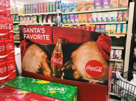 An ad for Coca-Cola at a local grocery store, buy it because it is Santa's favorite!