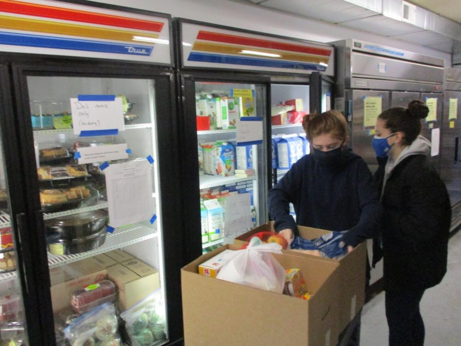 Alexis Evans(left) and Riley McDowell(right) packing a box full of food for a client at SVDP's pantry on Grant Avenue in Tigard.